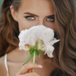 adorable-young-woman-holds-white-flower-before-her-face_8353-7213